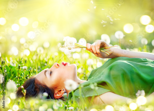 Beautiful young woman lying on the field in green grass and blowing dandelion flowers. Allergy free concept