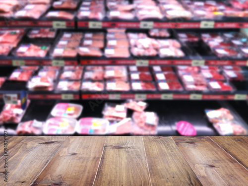Wood table top over blur background of supermarket with meat product on shelf.