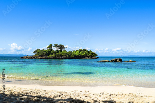 Fotografia White sandy beach, view over the blue turquoise water to a little island in the