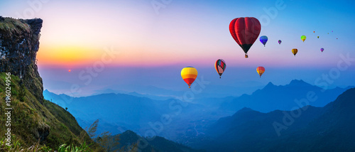 Leinwand Poster Colorful hot air balloons flying over mountain with sunrise at at phucheefa mountain