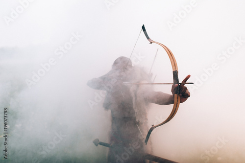 Photo archer in the fog