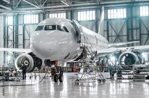 Passenger aircraft on maintenance of engine and fuselage repair in airport hangar.