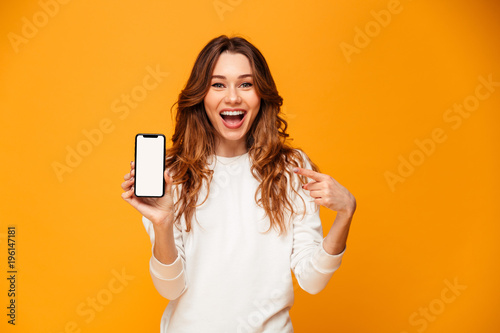 Fotomural Happy brunette woman in sweater showing blank smartphone screen