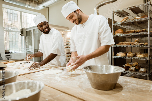 Photographie happy bakers kneading dough together at baking manufacture and talking