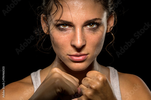 Fototapeta Intense female fighter stare with fist up in self defense training, powerful and