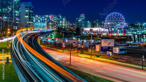 Fototapeta premium Długa ekspozycja centrum Vancouver, Kolumbia Brytyjska, Kanada. Jedno z najbardziej tętniących życiem miast Ameryki Północnej. Szlak świateł pociągów podniebnych, gwiazdy i błyszczy.