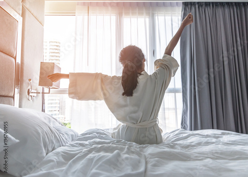 Stampa su Tela Easy lifestyle Asian woman waking up from good sleep in weekend morning taking s