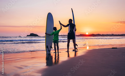 Father and son surfers stay on the sunset beach