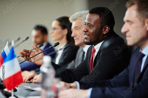 Fotografiet Young African-american politician explaining his opinion to audience during conf