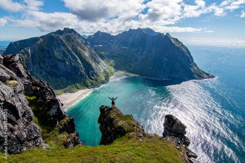 Carta da parati Adventurous woman looking down at Kvalvika Beach in Lofoten, Norway