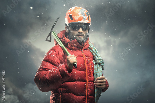 Obraz na płótnie Climber reaching the summit. Snow storm.