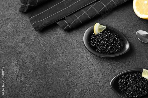 Bowls with black caviar on dark grey background