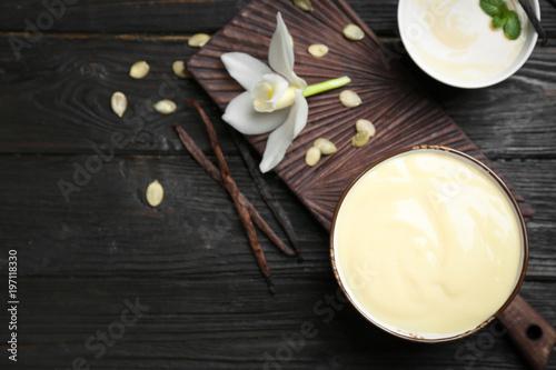 Fotografía Vanilla pudding, sticks and flower on wooden background