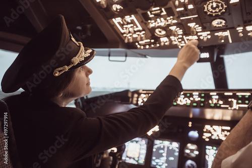 Slika na platnu Female pilot the captain of the plane prepares for take-off in the plane cockpit