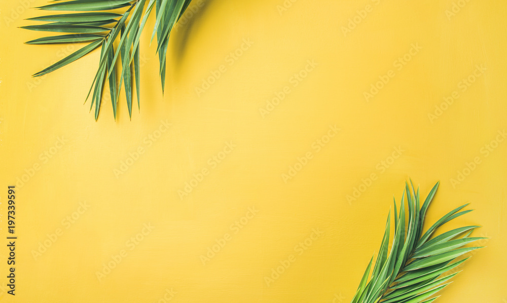 Flat-lay of green palm branches over yellow background, top view, copy space, wide composition. Summer vacation, travel or fashion concept