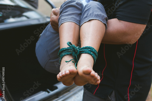 Leinwand Poster little girl with rope tied legs and hands in car,Criminal stealing child in human child traficking concept,children thief,Dangerous in the city