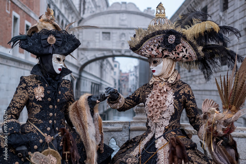 Venice Carnival: Two woman in costumes and masks, carrying feathered bird and bi Fototapeta