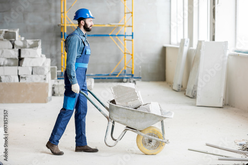 Fotografia Builder carrying blocks on a wheelbarrow at the construction site indoors