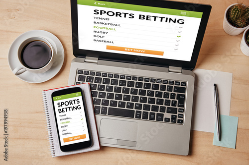Fotografía Sports betting concept on laptop and smartphone screen over wooden table