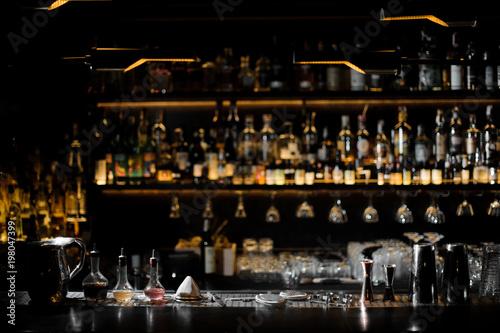 Blurred background of dark bar with barman essentials