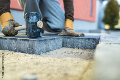 Canvas Print Workman tamping down a new paving brick