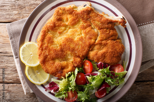 Photo Veal milanese (cotoletta alla milanese) with lemon and fresh vegetable salad close-up