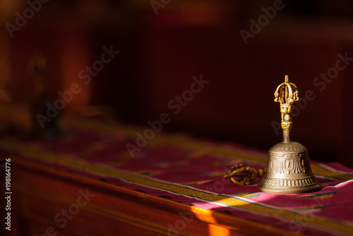 Ritual hand bell in the Buddhist temple as the enlightenment symbol, has got to a sunlight beam.