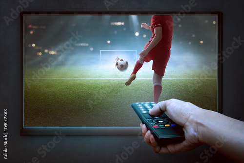 People hands with remote watching football game