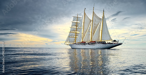 Sailing ship against the background of beautiful sky and ocean. Yachting. Sailing