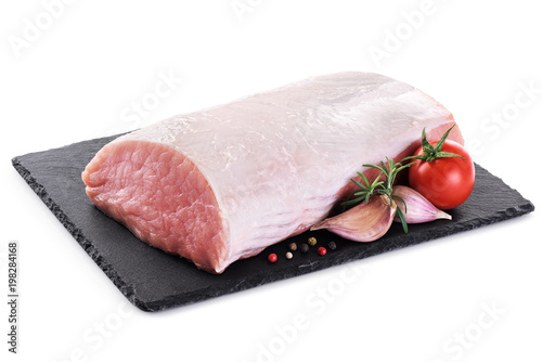 Raw sliced pork loin with tomato, pepper, rosemary and garlic on the background of a slate board. Fresh meat.