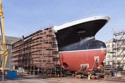 Photo Hull of ship under construction at shipyard.