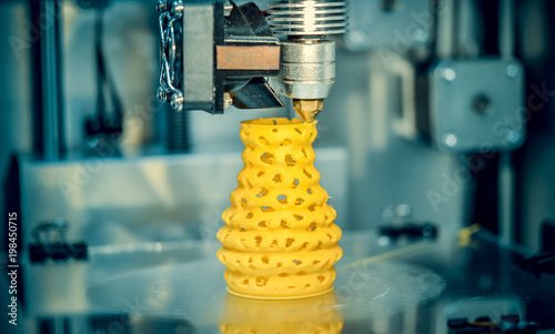 3d printer printing objects yellow form closeup. Modern technical 3D printing.