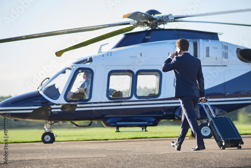 Stampa su Tela Rear View Of Businessman Walking Towards Helicopter Whilst Talking On Mobile Pho