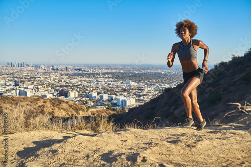 Fotografia fit african american woman running at runyon canyon with los angeles in backgrou
