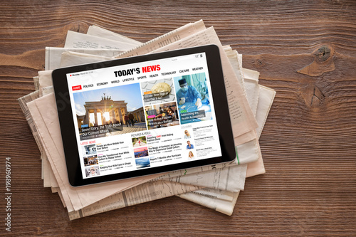 Tablet with news website on stack of newspapers. All contents are made up.
