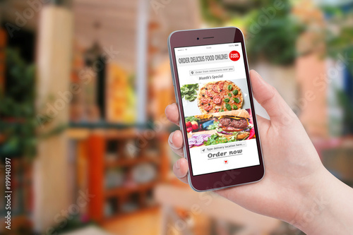 Female hand holding smartphone and ordering food with app in restaurant