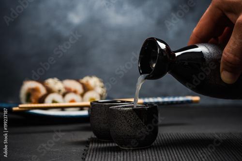 Man pouring sake into sipping bowl