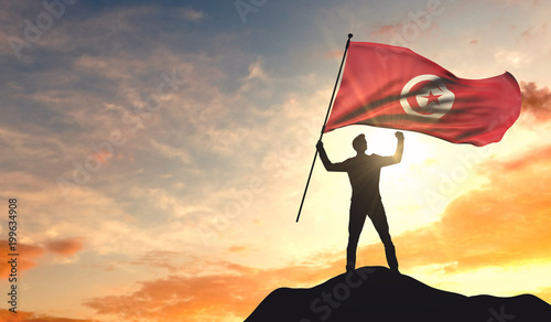 Fotografie, Obraz Tunisia flag being waved by a man celebrating success at the top of a mountain
