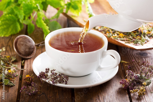 Fotografia pouring tea into a cup