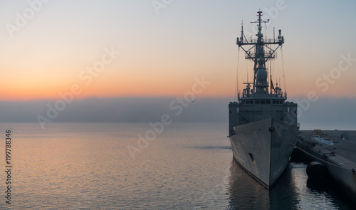 Photo A background of a war ship in the naval base during sunset