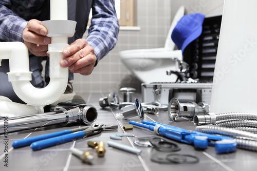 Slika na platnu plumber at work in a bathroom, plumbing repair service, assemble and install con