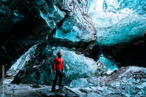 Fotografia, Obraz adventurer inside a blue ice cave in iceland