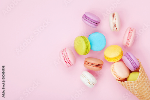 Fotografie, Obraz Waffle cone with colorful macaron or macaroon on pink pastel background top view