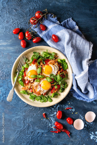 Traditional Israeli Cuisine dishes Shakshuka. Fried egg with vegetables tomatoes and paprika in ceramic plate with cloth, herbs and ingredients above over blue texture background. Top view, space.