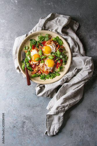 Traditional Israeli Cuisine dishes Shakshuka. Fried egg with vegetables tomatoes and paprika in ceramic plate with cloth and coriander herbs over blue texture background. Top view, space.