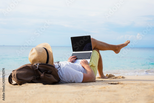 Relaxed man with laptop on the beach