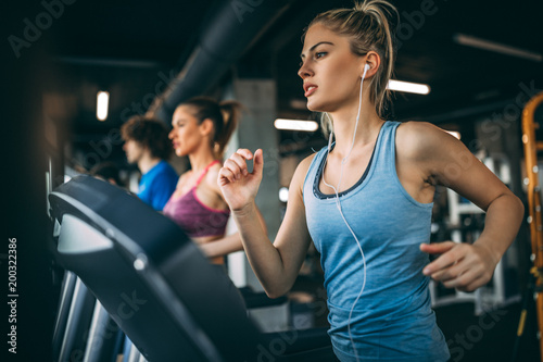 Young people running on a treadmill in health club. Fototapeta
