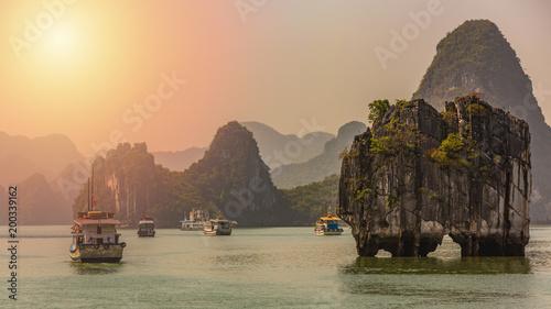 Fotografia Beautiful sunset tourist junks boat anchor floating among limestone cliffs rocks at Ha Long Bay, South China Sea, Vietnam, Southeast Asia