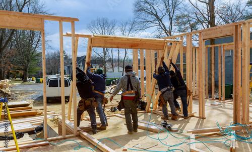 Fényképezés Construction Worker Using nail gun On wood building frame against