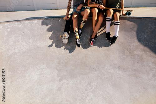 Legs of female skaters sitting together at skate park